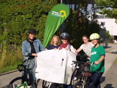 Frauen mit Fahrrädern zeigen eine Radkarte
